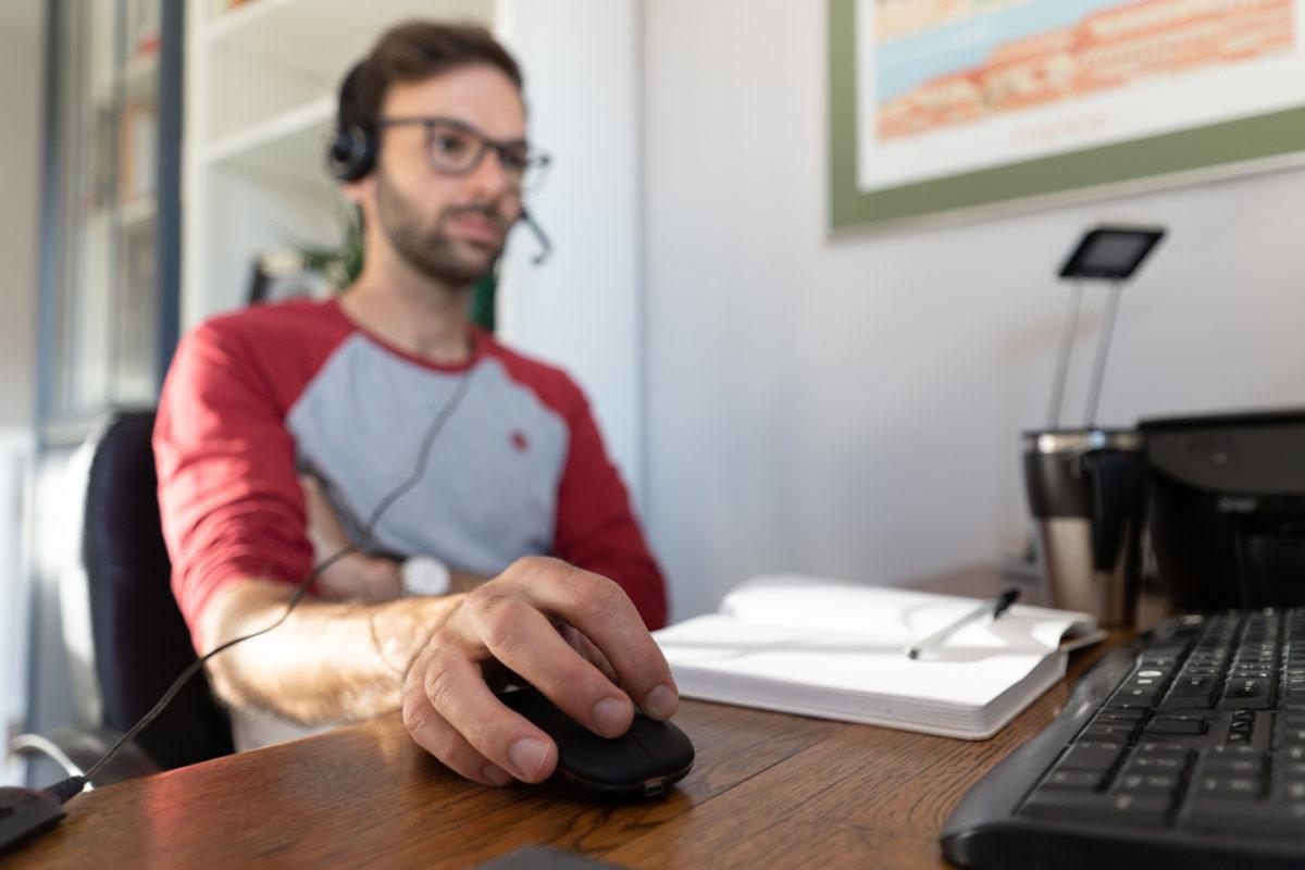 Informaticien en télétravail  muni d'un casque pour recevoir les appels de ses collègues. Sa main droite est posée sur la souris et un cahier ouvert repose devant lui. Toulouse, 26 novembre 2020.