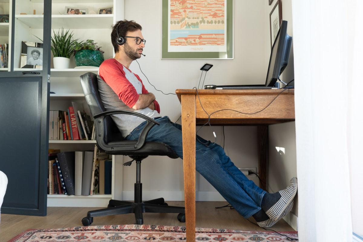 En chaussettes et pantoufles, un informaticien chez lui en télétravail perplexe devant son ordinateur. Toulouse, 26 novembre 2020.