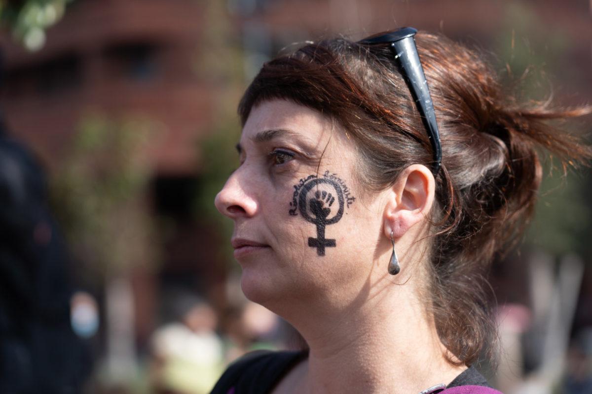 """Portrait de profil d'une manifestante sur le visage de laquelle est dessiné le logo poing levé de la lutte féministe avec l'inscription """"Révolution féministe"""" lors de la manifestation pour la journée sur les droits des femmes. Toulouse, 8 mars 2021."""