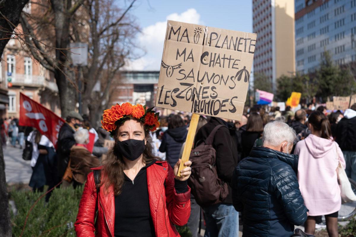 """Une manifestante montre une pancarte sur laquelle on peut lire """"Ma planète, ma chatte, sauvons les zones humides"""" lors de la manifestation pour la journée sur les droits des femmes. Toulouse, 8 mars 2021."""