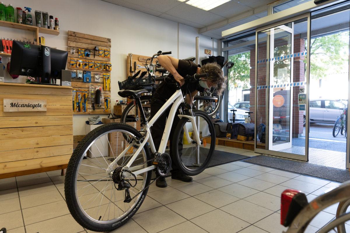 Une employé de la boutique de réparation de vélo Mécanicycle prend en charge un vélo pour le réparer. Toulouse, le 23 avril 2021.