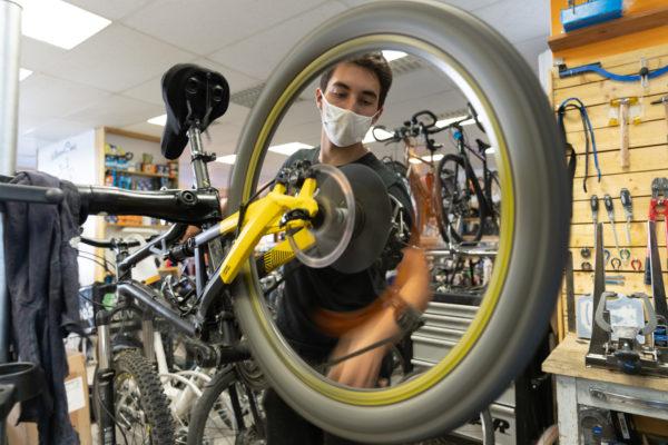 Un employé de la boutique de réparation de vélo Mécanicycle vérifie le mouvement d'une roue de vélo. Toulouse, le 23 avril 2021.