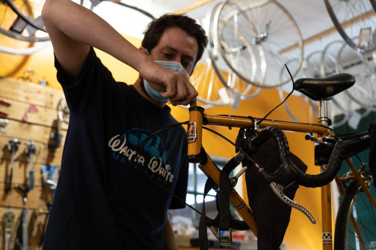 Un employé de la boutique de réparation de vélo Mécanicycle graisse le tube de direction d'un vélo. Toulouse, le 23 avril 2021.