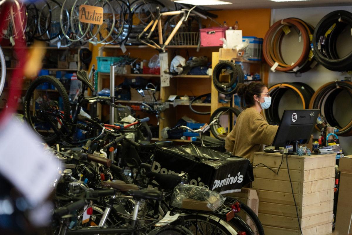 Vue sur l'intérieur d'une boutique de réparations de vélos. En premier plan, des vélos. En arrière plan, une employée masquée devant son ordinateur.