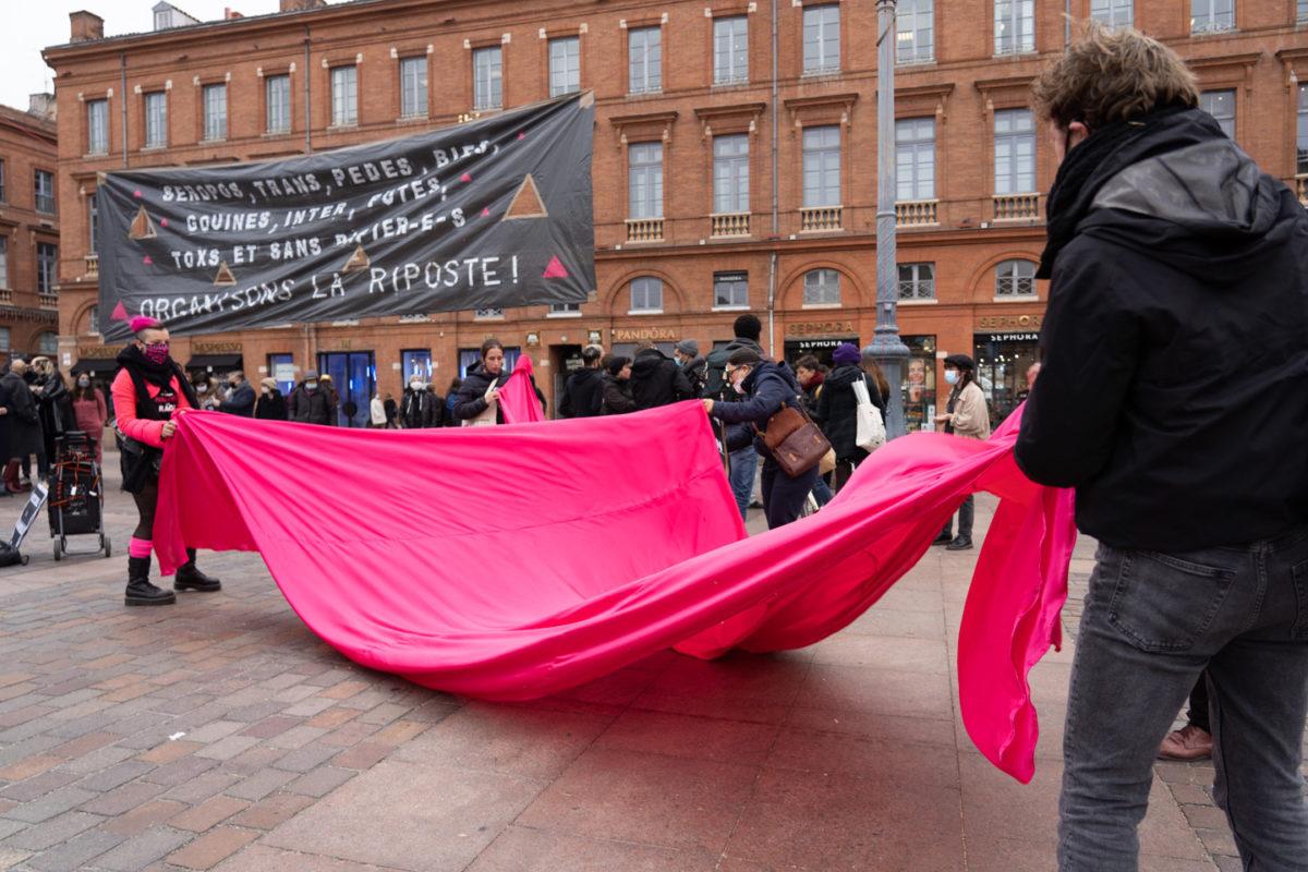 Des militants d'Act Up déploient un grand triangle rose en tisse sur les pavés de la place du Capitole, à Toulouse, à l'occasion du rassemblement organisé par ActUp Sud-Ouest pour la journée mondiale contre le VIH/SIDA.  Ils dénoncent notamment la politique sanitaire du gouvernement pendant la crise du Covid. Toulouse, le 1er décembre 2020.