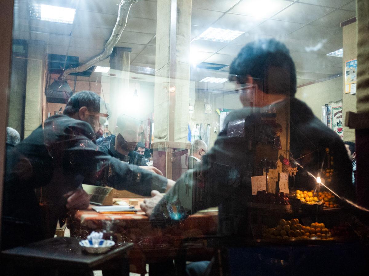 """Un groupe d'hommes jouent à """"Okey"""" - un jeu de dominos - dans une maison de thé traditionnelle uniquement fréquentée par des hommes. En reflet dans la vitrine, un l'étal d'un marchand de légumes. Diyarbakir (Turquie), novembre 2010."""
