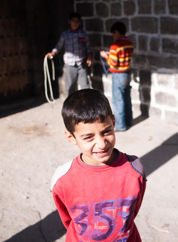 Des enfants jouent dans la rue. Un d'entre eux pose pour la photographie. Diyarbakir (Turquie), novembre 2010.