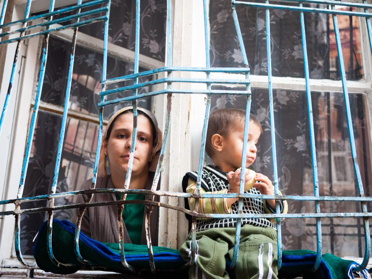 Une jeune femme kurde et son enfant regardent les passants depuis la fenêtre fermée de barreaux de leur domicile. Diyarbakir (Turquie), novembre 2010.