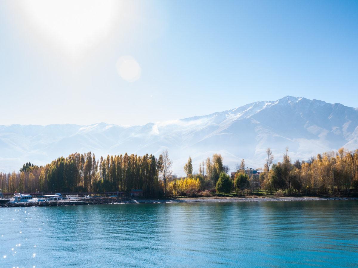Les rives boisées du lac Van, un petit port touristique et les hautes montagnes au sud du lac vus depuis le bâteau menant à l'île d'Akdamar.  Van (Turquie), novembre 2010.
