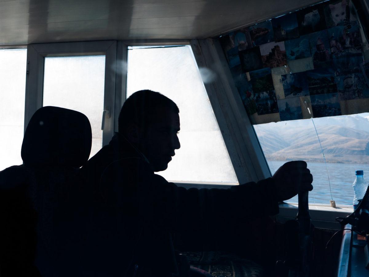 Silhouette du barreur opérant le bateau menant à l'île d'Akdamar dans le lac de Van. Sur le pare-brise, des photos et cartes postales typiques de la région. Van (Turquie), novembre 2010.