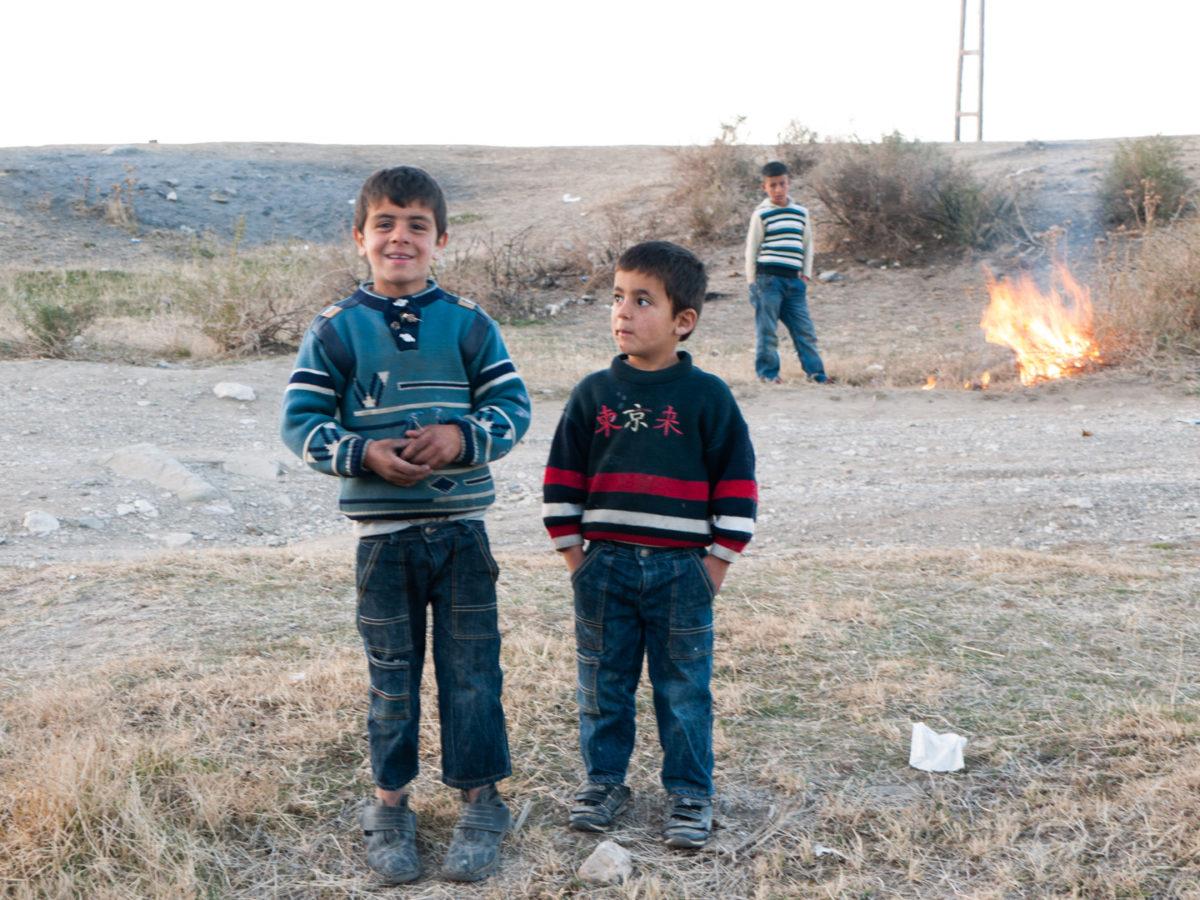De jeunes garçons ont allumé un petit feu de broussailles dans un terrain vague à proximité de la forteresse de Van. Van (Turquie), novembre 2010.