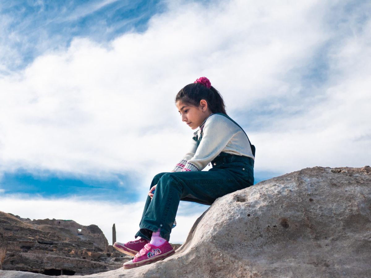 Une petite fille assise sur un promontoir rocheux. Hasankeyf (Turquie), novembre 2010.