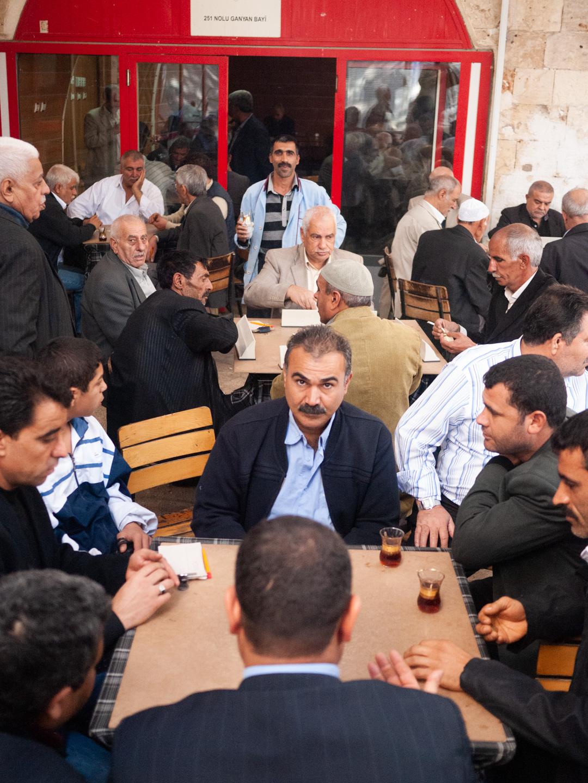 """Sur la terrasse d'une maison de thé traditionnelle uniquement fréquentée par des hommes, ces derniers boivent du thé et jouent à """"Okey"""" - un jeu de dominos . Urfa (Turquie), novembre 2010."""