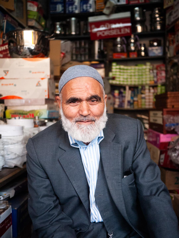 Un vieil homme barbu et coiffé d'un chapeau de prière devant sa quincaillerie. Urfa (Turquie), novembre 2010.