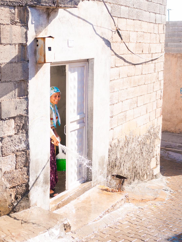 Une jeune femme en train de faire le ménage arrose le pas de la porte de son domicile. Urfa (Turquie), novembre 2010.