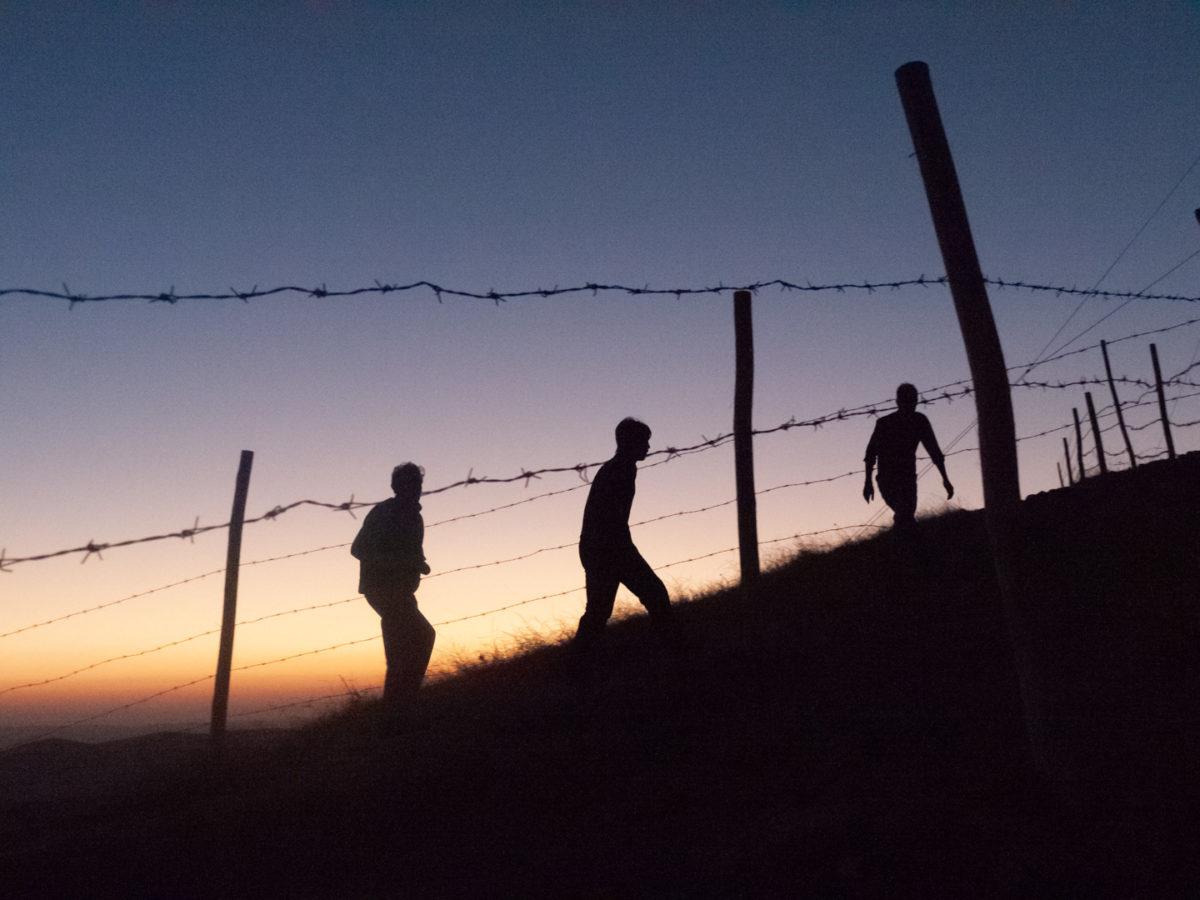 Trois touristes gravissent la colline de Göbeklitepe alors que le soleil se couche. Göbeklitepe (Turquie), novembre 2010.