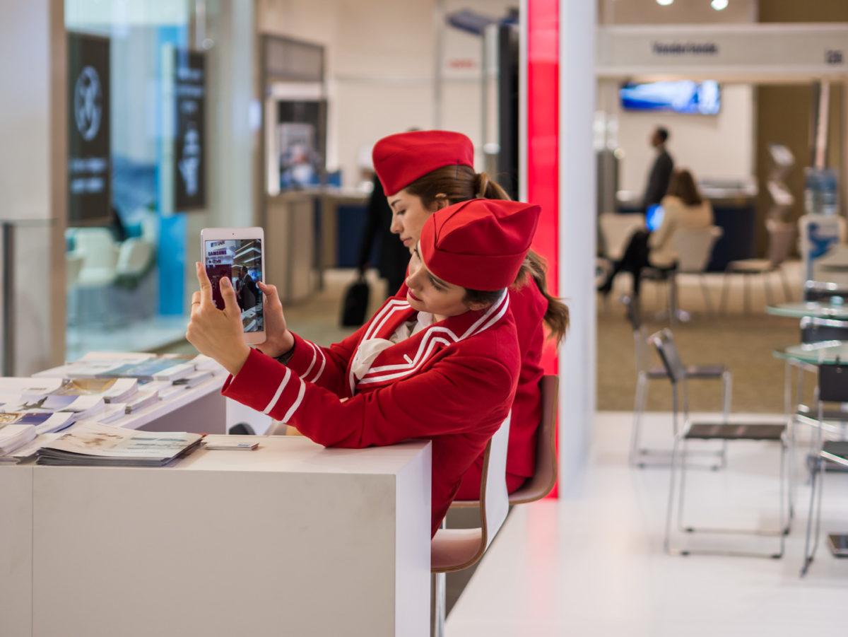 """Deux hôtesses d'accueil patientent à leur stand pendant le salon Airport Exchange au centre Lutfi Kirdar. L'une d'entre elles semble prendre une photo avec une tablette. Istanbul - Turquie - décembre 2015. © Grégory Dziedzic Photography. (Portfolio """"Sur le lieu de travail"""")"""