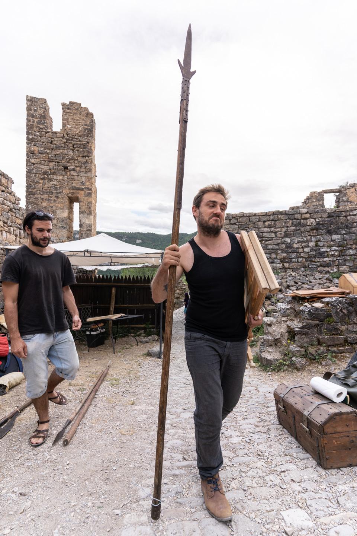 """Un membre de la compagnie médiévale """"Les Faydits d'Oc"""" porte une lance en amont de leur représentation au château de Peyrelade. Rivière-sur-Tarn, août 2020."""