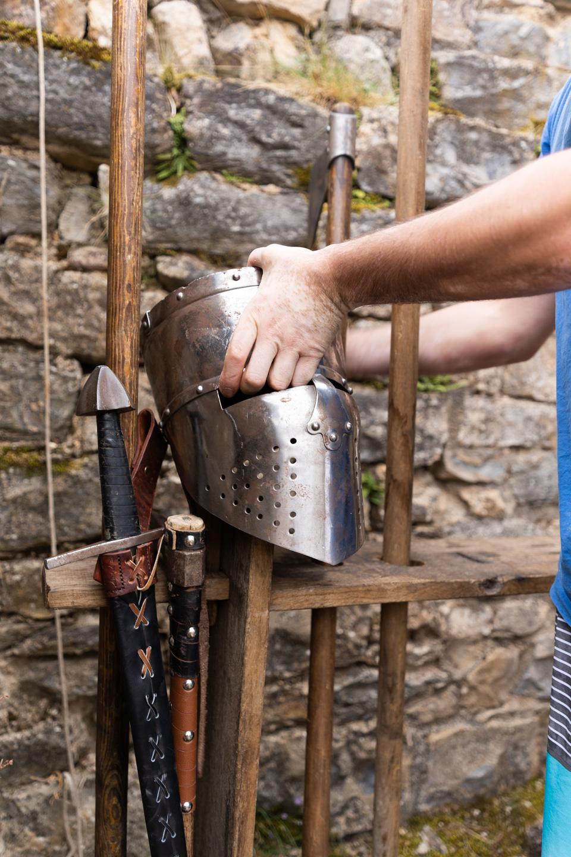 """Un membre de la compagnie médiévale """"Les Faydits d'Oc"""" se saisit d'un heaume métallique en amont de la représentation au château de Peyrelade. Rivière-sur-Tarn, août 2020."""