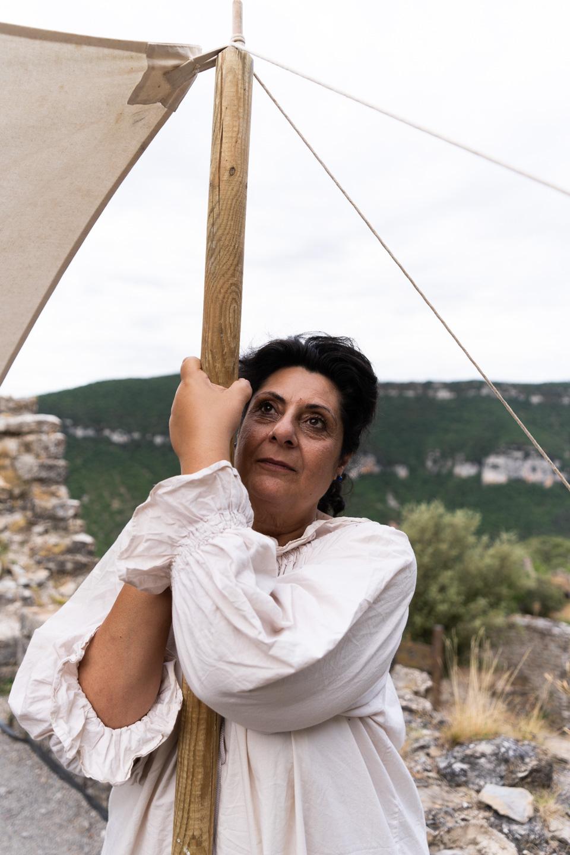 Dame Rita, de la compagnie médiévale Les Faydits d'Oc, participe au montage de la tente qui va abriter le repas de la troupe au château de Peyrelade. Rivière-sur-Tarn, août 2020.