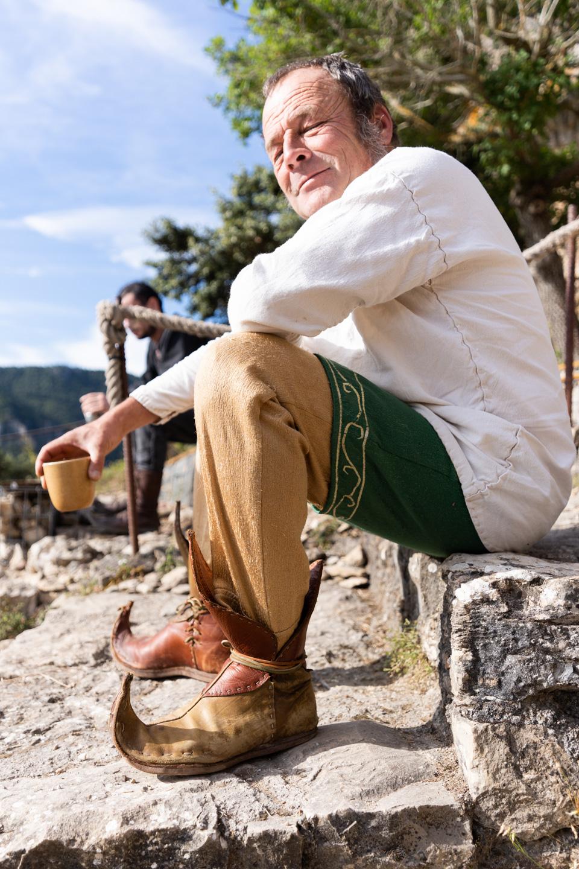 """Bruno est Tapaillo, fou du roi dans la compagnie médiévale """"Les Faydits d'Oc"""". Il se prépare à jouer devant les visiteurs du château de Peyrelades. Rivière-sur-Tarn, août 2020."""