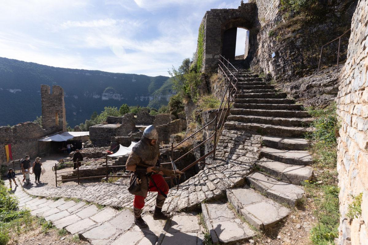 """Un arbaletrier joué par un membre de la compagnie médiévale """"Les Faydits d'Oc"""" gravit les marches du château de Peyrelade pour rejoindre son poste. Rivière-sur-Tarn, août 2020."""