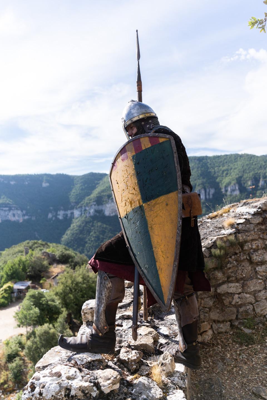 """Un soldat portant lance et bouclier joué par un membre de la compagnie médiévale """"Les Faydits d'Oc"""" fait la vigie sur les murailles du château de Peyrelade. Rivière-sur-Tarn, août 2020."""