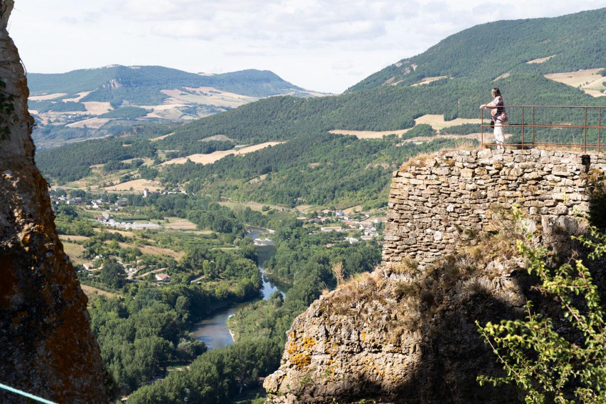 Une femme visitant le château de Peyrelade contemple les gorges du Tarn depuis un chemin de promenade du château. Rivière-sur-Tarn, août 2020.