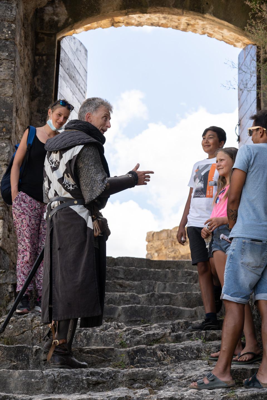 Messire Pons, un membre fondateur de la compagnie des Faydits d'Oc, discute avec des visiteurs lors de leur représentation au chiateau de Peyrelade. Rivière-sur-Tarn, août 2020.