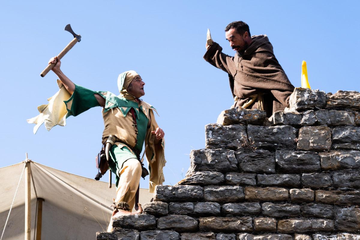 """Tapaillo, fou du roi dans la compagnie médiévale """"Les Faydits d'Oc"""", manace frère Tancrède avec une hachette lors d'une représentation de la troupe au château de Peyrelade. Rivière-sur-Tarn, août 2020."""
