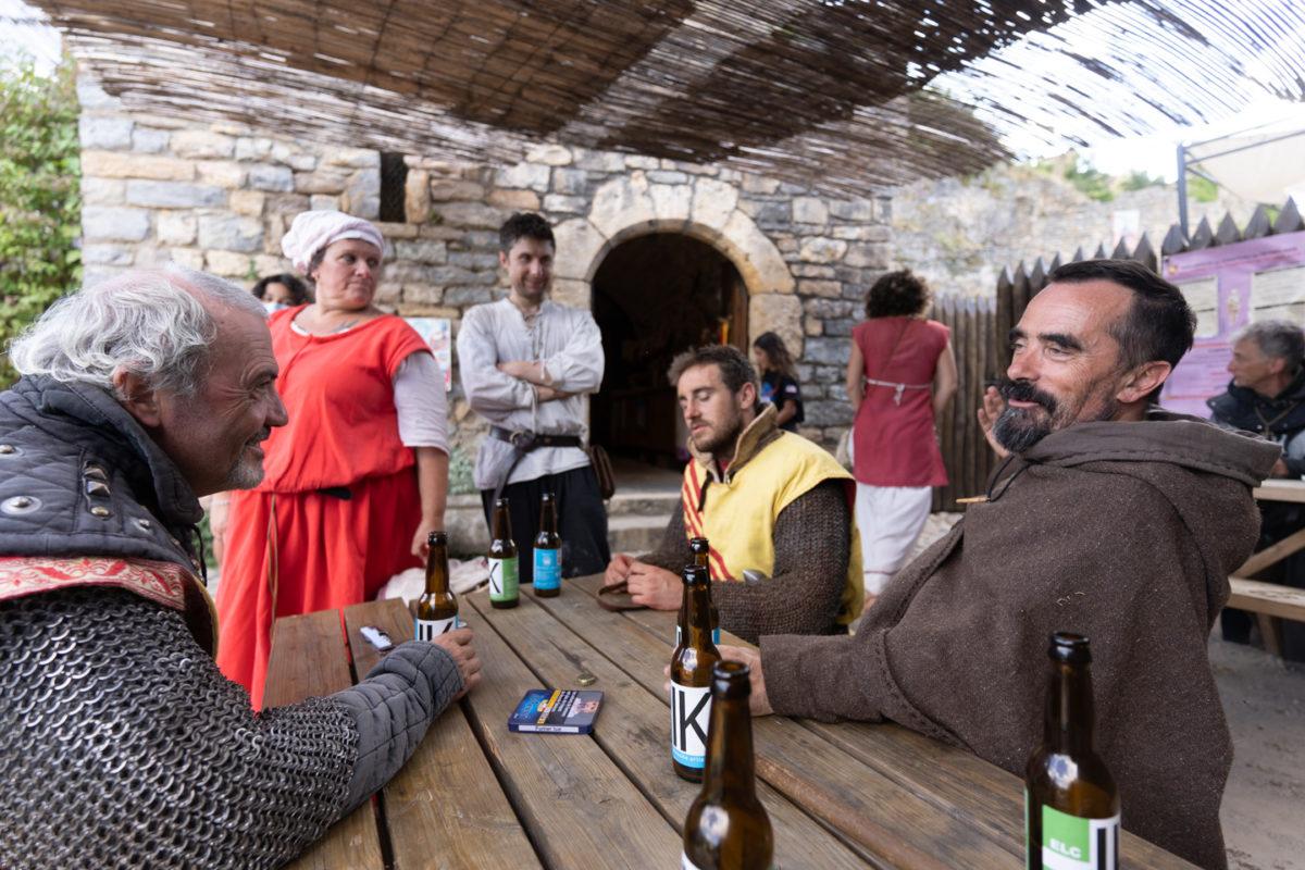 """Les membres de la compagnie médiévale """"Les Faydits d'Oc"""" font une pause à la buvette du château de Peyrelade, où la troupe s'est installée pour deux jours et enchaînes démonstrations et représentations. Pendant la durée de leur séjour sur un site, il est très rare qu'ils quittent ainsi les personnages qu'ils incarnent. Rivière-sur-Tarn, août 2020."""