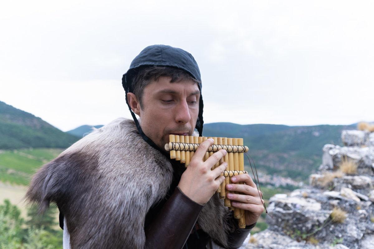 """Revêtu d'une peau de bête, Loïc, membre de la compagnie médiévale """"Les Faydits d'Oc"""", joue un air de flûte de Pan sur un promontoire du château de Peyrelade. Derrière lui, les gorges du Tarn. Rivière-sur-Tarn, août 2020."""