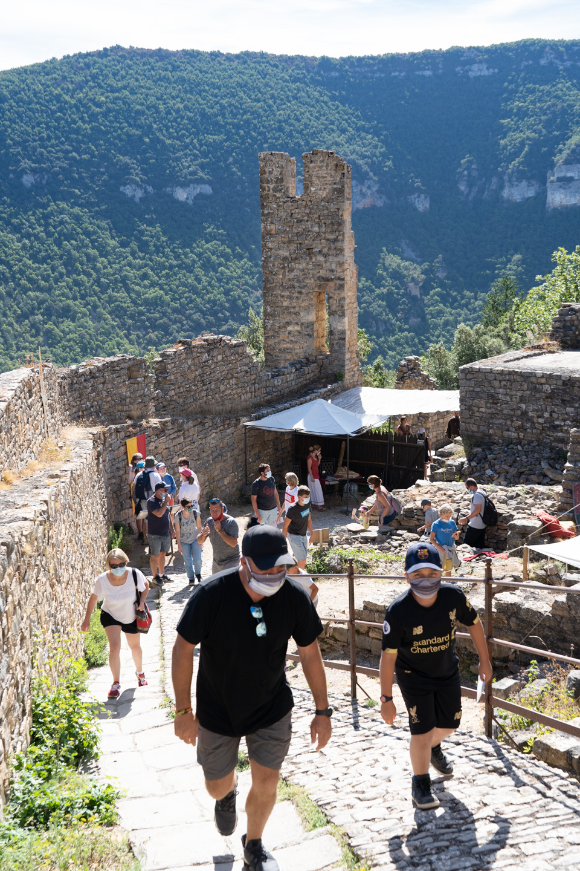 Des touristes arrivent dans le château de Peyrelade et commencent à en gravir les marches.  Ils portent des masques en raison de la situation sanitaire liée au Covid-19. Rivière-sur-Tarn, août 2020.