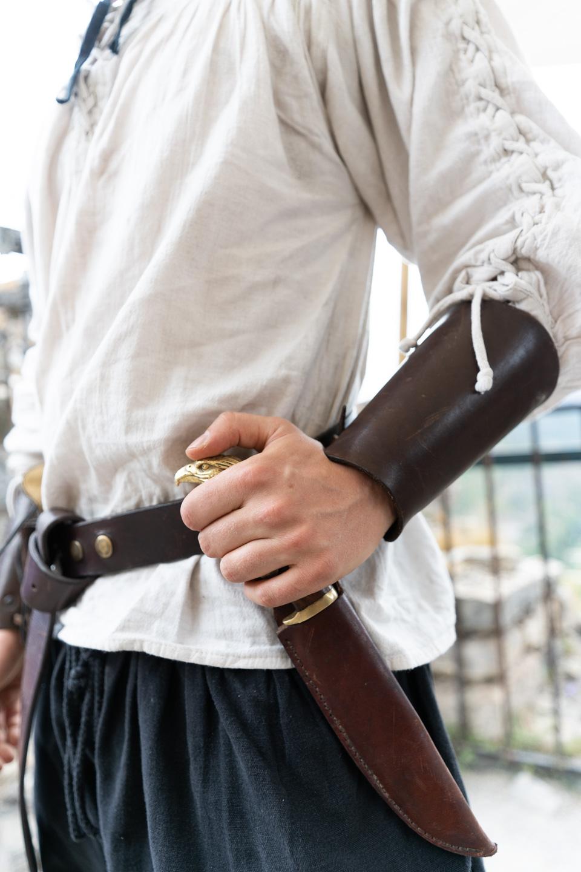 """Un membre de la compagnie médiévale """"Les Faydits d'Oc"""" en costume d'époque met la main sur le poignard orné d'une tête d'aigle à sa ceinture en amont d'une représentation au château de Peyrelade. Rivière-sur-Tarn, août 2020."""