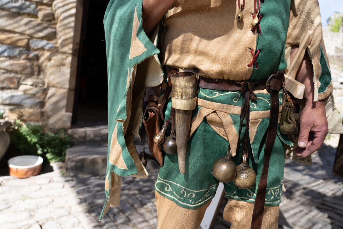 """Tapaillo, fou du roi dans la compagnie médiévale """"Les Faydits d'Oc"""", a de nombreux accessoires à sa ceinture, dont une corne pour boire ainsi qu'une impressionnant paire de grelots pendant devant son entrjeambe. Il se prépare à jouer devant les visiteurs du château de Peyrelade. Rivière-sur-Tarn, août 2020."""