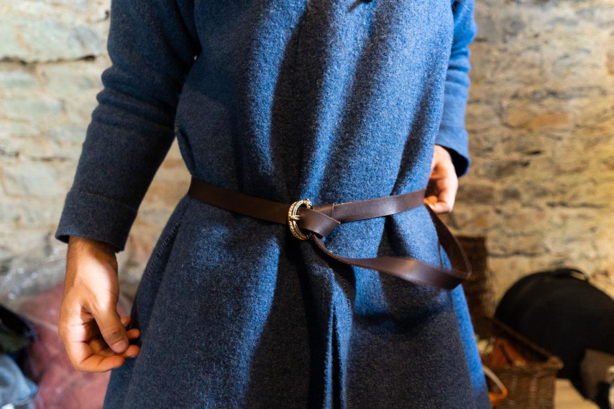 """Un membre de la compagnie médiévale """"Les Faydits d'Oc"""" en costume d'époque ajuste sa ceinture en amont d'une représentation au château de Peyrelade. Rivière-sur-Tarn, août 2020."""
