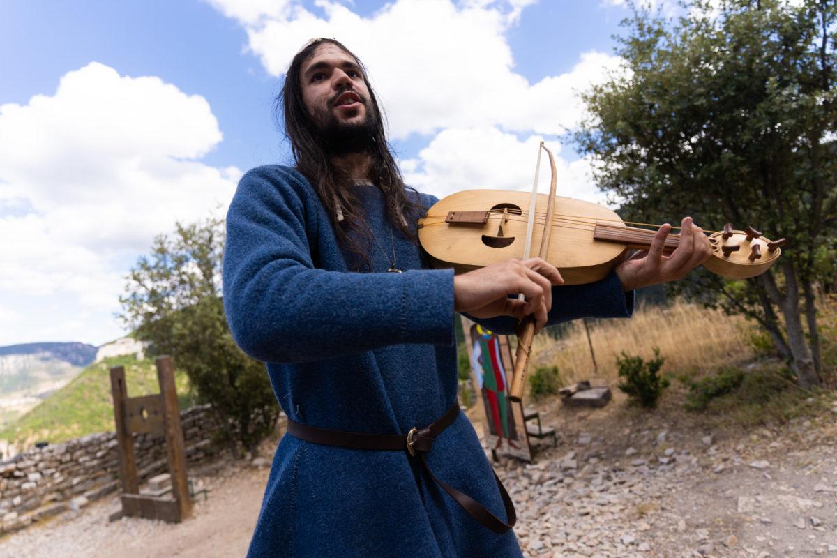 """Bohémond le troubadour, membre de la compagnie médiévale """"Les Faydits d'Oc"""", joue de la viole pendant une représentation au château de Peyrelade. Rivière-sur-Tarn, août 2020."""