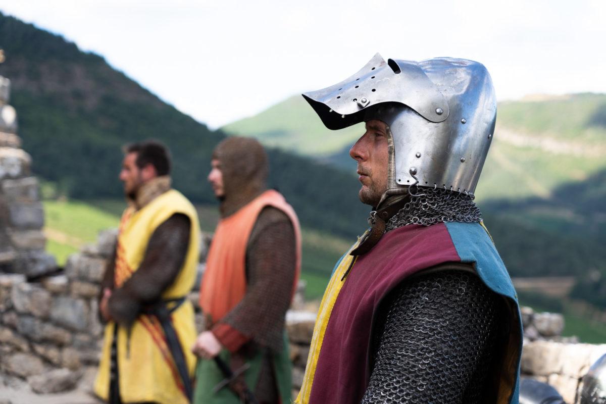 """Revêtu de son heaume à la visière levée et de sa côte de maille, Loïc, membre de la compagnie médiévale """"Les Faydits d'Oc"""", a le regard perdu hors champ pendant une représentation au château de Peyrelade. Derrière lui, deux autres chevaliers et les gorges du Tarn. Rivière-sur-Tarn, août 2020."""