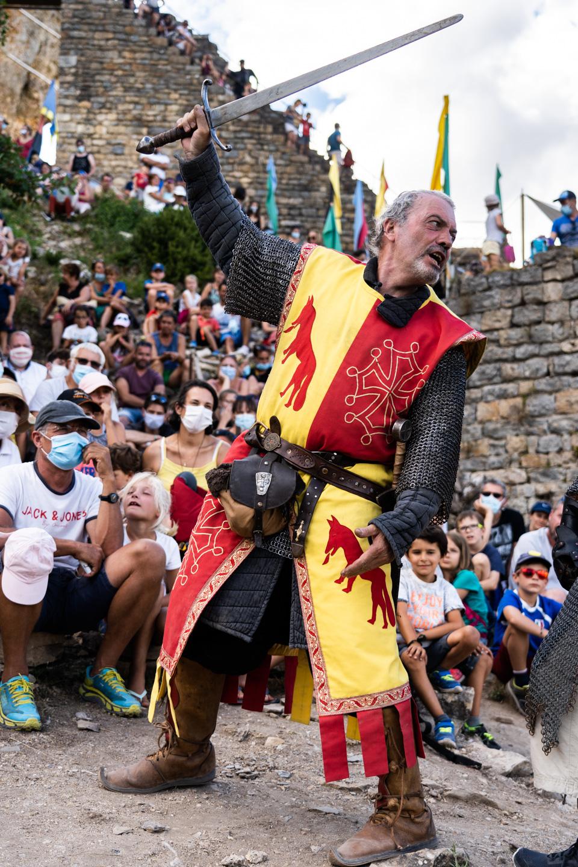 """Messire Roger, de la compagnie médiévale """"Les Faydits d'Oc"""", démontre le maniement de l'épée pendant une représentation devant un parterre de spectateurs au château de Peyrelades. Les touristes portent un masque en raison de la situation sanitaire liée au Covid-19. Rivière-sur-Tarn, août 2020."""