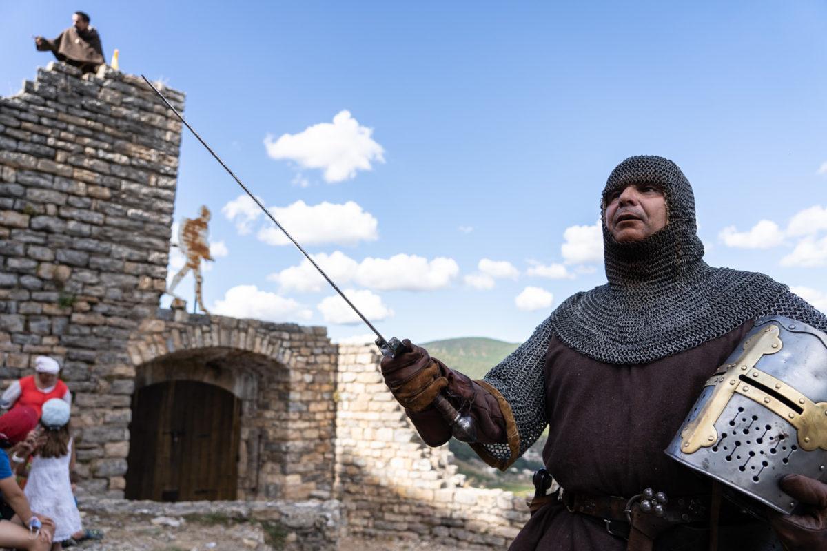 """Sire Yvan, de la compagnie médiévale """"Les Faydits d'Oc"""", brandit sont épée le casque à la main pendant une représentation au château de Peyrelade. Rivière-sur-Tarn, août 2020."""