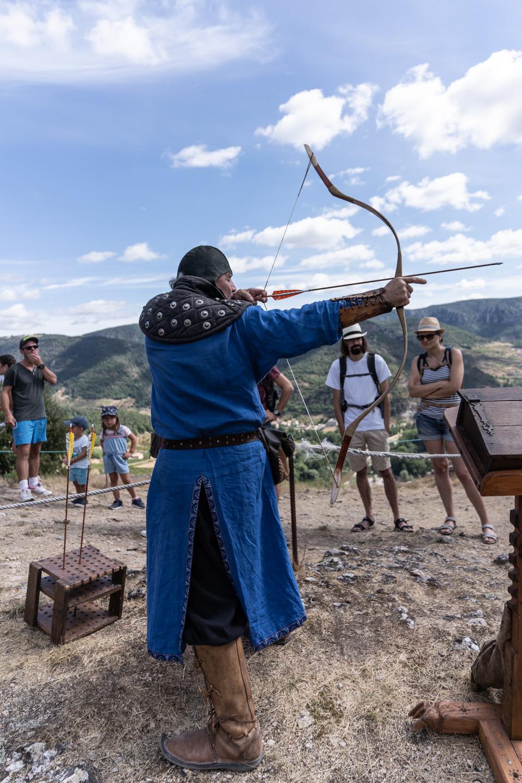 """Messire Roger, de la compagnie médiévale """"Les Faydits d'Oc"""", fait une démonstration de tir à l'arc devant des visiteurs du château de Peyrelade. Rivière-sur-Tarn, août 2020."""