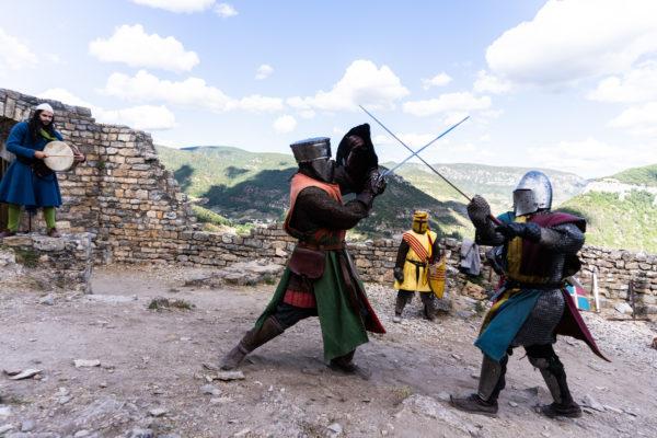 """Des membres de la compagnie médiévale """"Les Faydits d'Oc"""" en tenue de chevaliers croisent le fer pendant une représentation au château de Peyrelade sous les regars d'un troubadour et d'un troisième chevalier. Rivière-sur-Tarn, août 2020."""