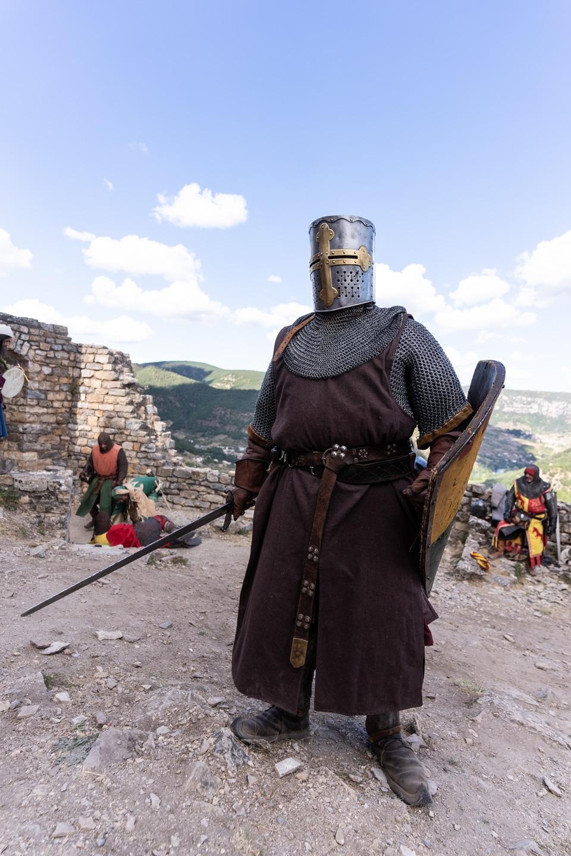 """Sire Yvan, de la compagnie médiévale """"Les Faydits d'Oc"""", prêt au combat avec épée, bouclier, heaume et cote de maille pendant une représentation au château de Peyrelade. Rivière-sur-Tarn, août 2020."""