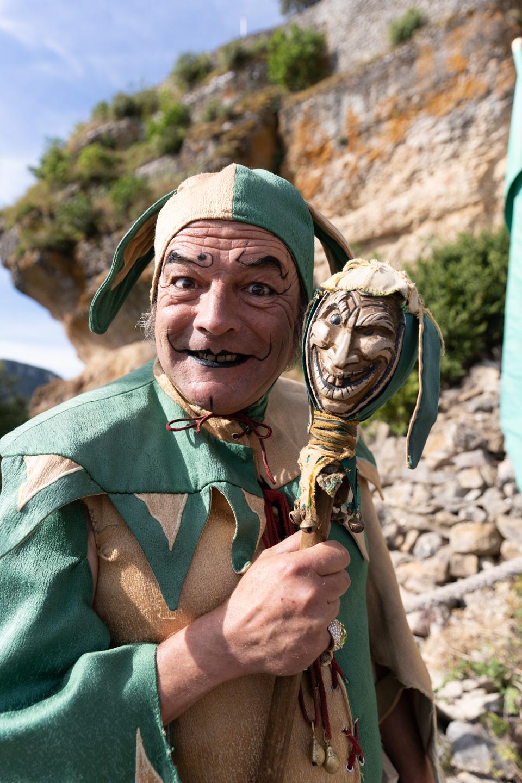 """Tapaillo, fou du roi dans la compagnie médiévale """"Les Faydits d'Oc"""", manace frère Tancrède lors d'une représentation de la troupe au château de Peyrelade. Rivière-sur-Tarn, août 2020."""