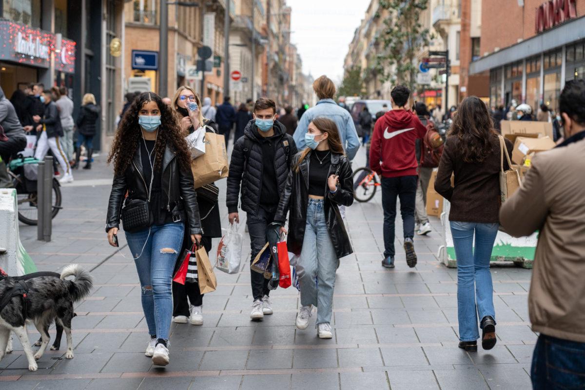 Un groupe de jeunes portent leurs achats sur la rue Alsace-Lorraine pendant les courses de Noël en centre ville. Toulouse, le 21 décembre 2020.