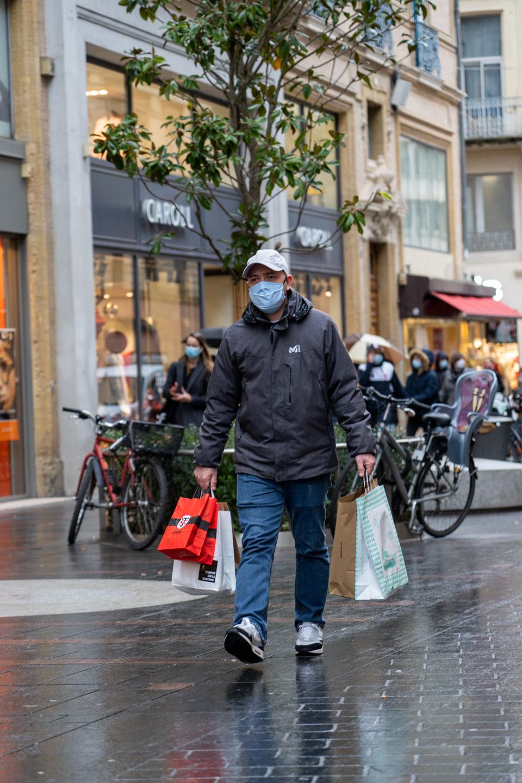 Un homme porte de nombreux sacs d'achats sur la rue Alsace Lorraine pendant les courses de Noël en centre ville. Toulouse, le 21 décembre 2020.