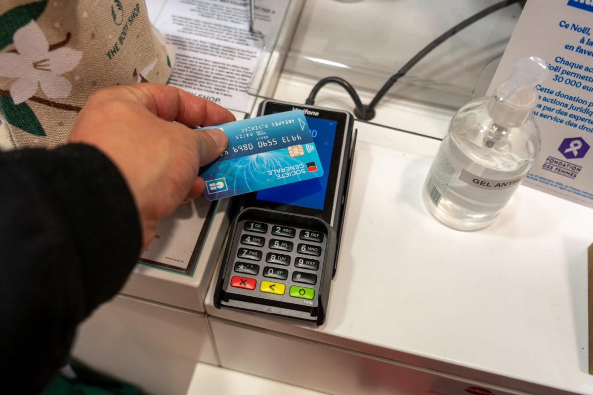 Un consommateur règle ses courses de Noel par carte bleue, une bouteille de gel hydroalcoolique posée à côté du terminal de paiement. Toulouse, le 21 décembre 2020.