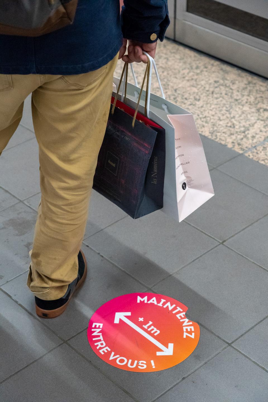 Plan rapproché sur un usager du métro ayant fait ses courses de Noël. Il est debout sur le quai, à côté d'une étiquette prônant la distanciation physique dans le cadre des mesures barrières contre la Covid-19. Toulouse, le 21 décembre 2020.
