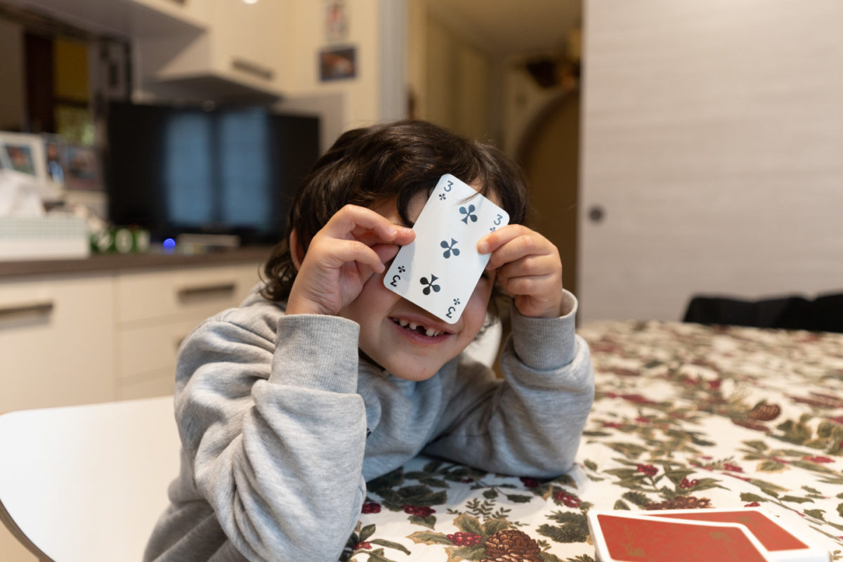 Théo cache bien son jeu pendant une partie de cartes. Alors que se profile le spectre de possibles restrictions sanitaires, les vacances de Noël ont été l'occasion pour les parents d'enfants en bas âge d'expérimenter le confinement en famille. Les jeux de société traditionnels ont connu un essor commercial considérable pendant l'année 2020. Toulouse, décembre 2020.
