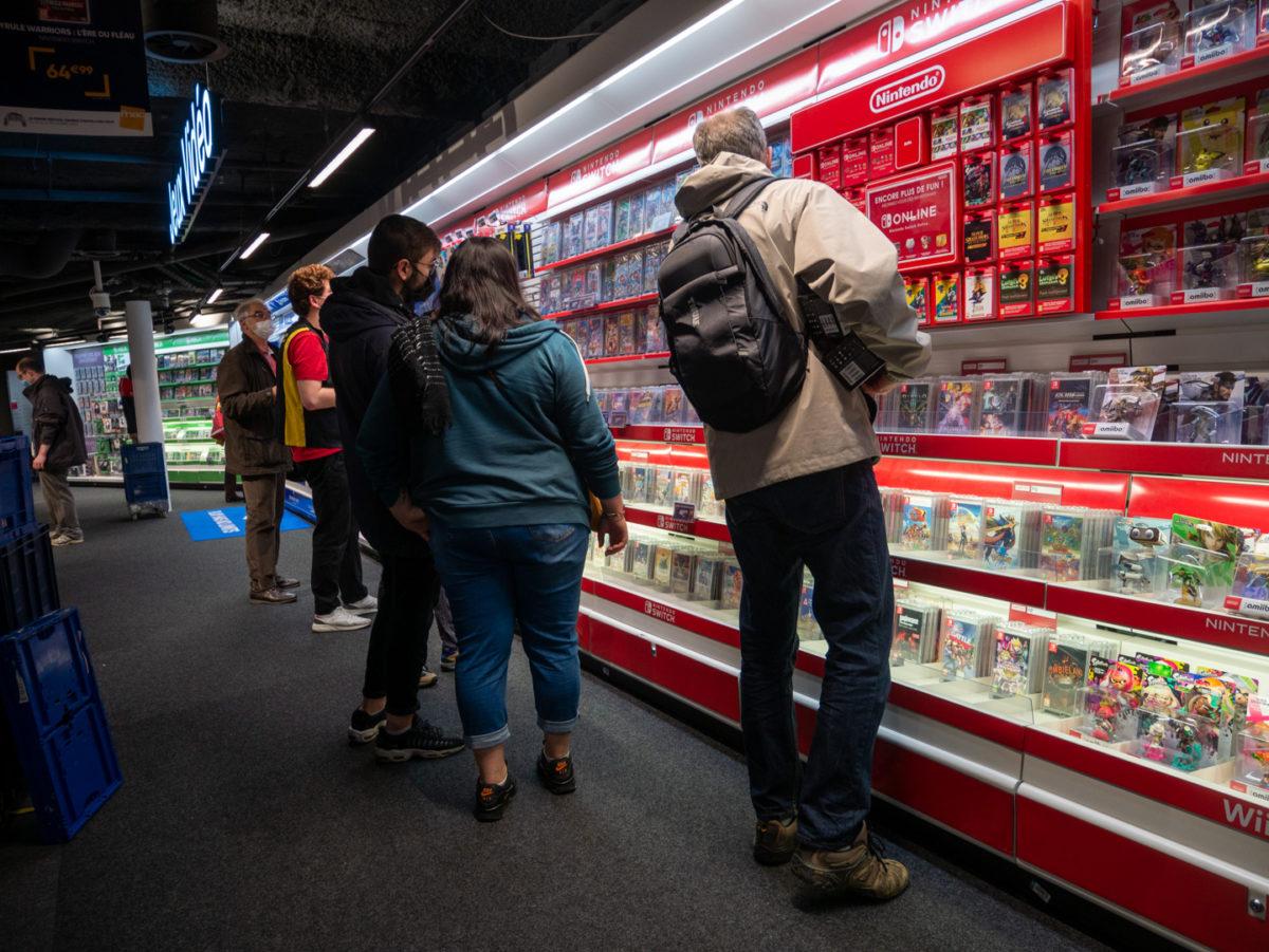 Des consommateurs regardent le rayon jeux vidéos d'une grande enseigne pendant les courses de Noël. Toulouse, le 21 décembre 2020.